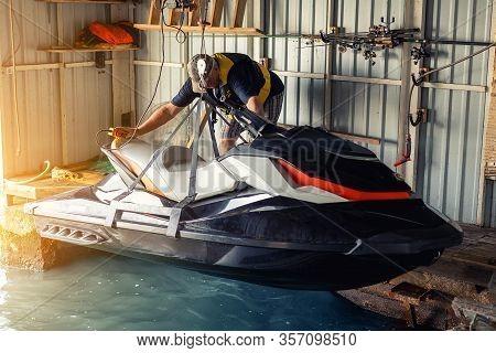 Senior Man Launching Or Lifting Modern Fast Jetski Hanged On Strpas With Wire Hoist Rail Crane For D