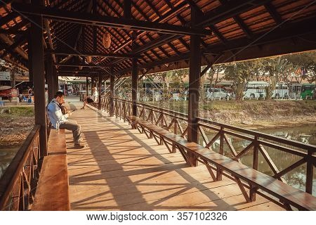 Siem Reap, Cambodia: People Sitting And Relaxing On Covered Pedestrian Bridge At Hot Day Of Historic