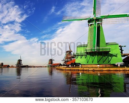 Windmill In Rotterdam On The Calm Lake Where It Reflects The Clear Sky And The Structure Of The Buil