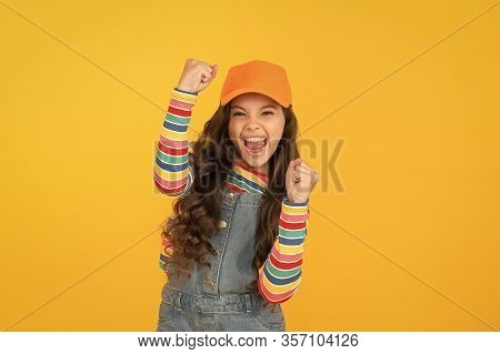 Happy Winner. Happy Little Girl Making Winning Gesture On Yellow Background. Cheerful Small Child Ha