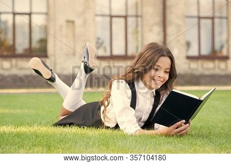 Read Every Day. Cute Small Child Read Library Book On Green Grass. Adorable Little Girl Learning To