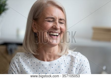 Happy Middle Aged Blonde Woman Laughing At Funny Joke.