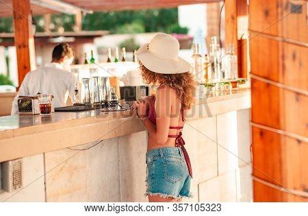 Happy Girl Female At Bar Pool On Hotel Resort, Asking To Barman Make An Order. Drinking At The Bar.