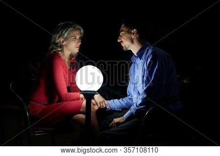 Beautiful Blonde Woman In Red Dress, And A Man In Blue Shirt Sits Together In Darkness, Next To A Ba