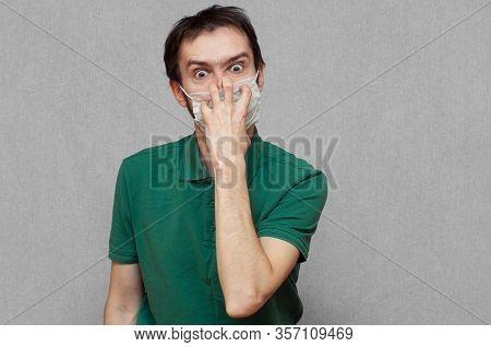 Man In Panic Trying Tear Off A Medical Mask. Virus Mutation, Panic, Paranoia