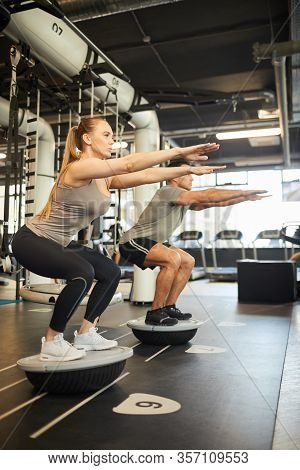 Full Length Side View At Sportive Couple Doing Balance Exercises During Workout In Modern Gym, Copy