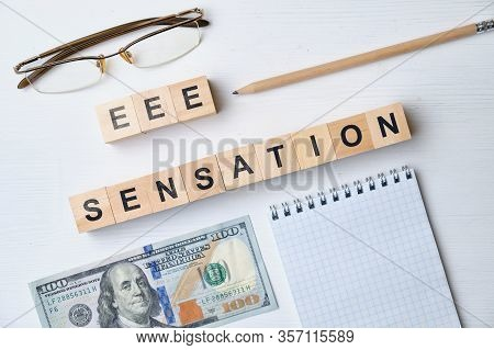 Modern Business Buzzword - Eee Sensation. Top View On The Board, Glasses, Pencil, Dollar And Notepad