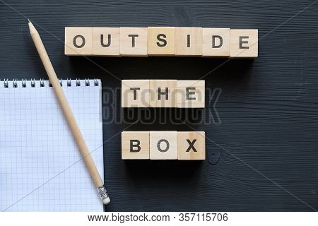 Modern Business Buzzword - Outside The Box. Top View On A Black Board, A Notebook And Pencil With Wo