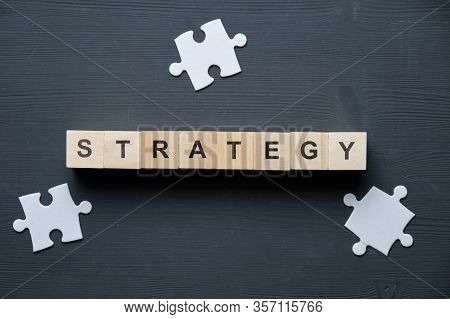 Modern Business Buzzword - Strategy. Top View On A Board With A Puzzle And Wooden Blocks. Close Up.