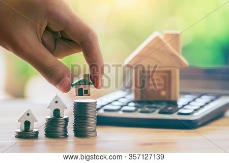 House On Coins And House Put On Calculator. Man's Hand Putting Home. Planning Savings Money