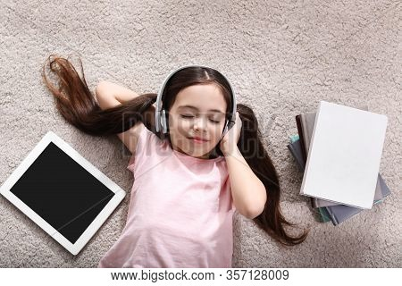 Cute Little Girl With Headphones And Tablet Listening To Audiobook On Floor Indoors, Flat Lay