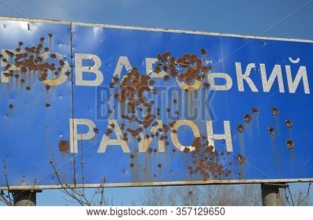 Bullet holes in a traffic sign. Incription - BROVARY DISTRICT (UKR). 1 km near Kiev. A large number of illegal weapons during the civil war. March 13, 2020 Kiev,Ukraine