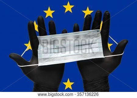 Doctor Holds Face Mask In Hands In Black Medical Gloves On Background Colors Flag Of European Union