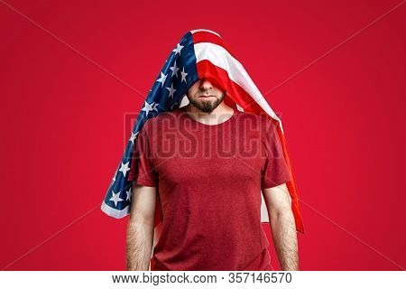 A Man With A Head Covered With An American Flag Stands Humbly On A Red Background. Copy Space. The C