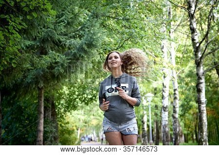 Beautiful Pregnant Woman Running In The Park. The Concept Of A Healthy Pregnancy And A Healthy Lifes