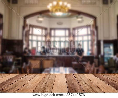 Wooden Table Top Over Blur Background Of Vintage Coffee Shop Interior With Europe Decoration Style.
