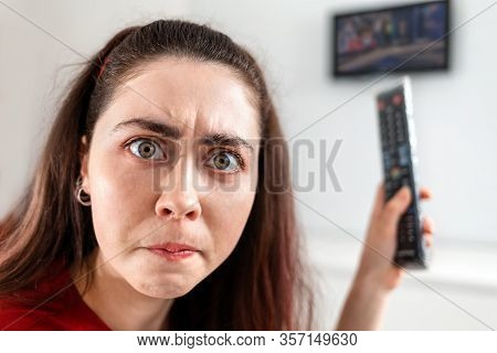 Close-up Portrait Of A Young Woman With A Frowning And Incredulous Face, Who Is Holding A Remote Con