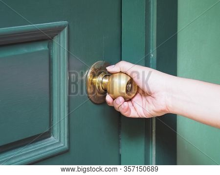 Woman Hand Holding Brass Vintage Knob And Opening Green Door.