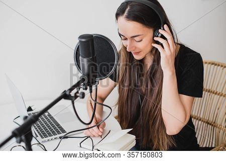 Attractive Young Woman Blogger With Long Black Hair Recording Online Podcast Using Her Laptop, Headp