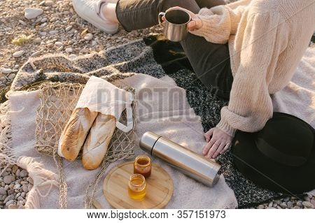 Young Woman In Knitted Sweater Having Picnic At Beach With Tea In Thermos And Fresh Baguettes In Wic
