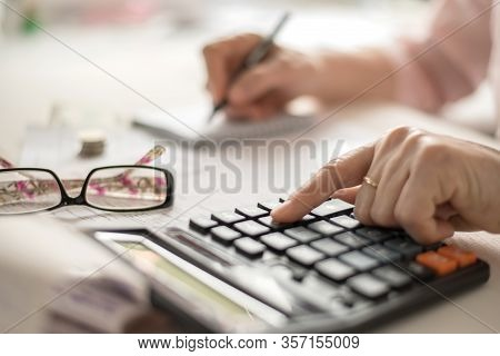 Pension Calculation Concept, Old Hands Counting Finances On A Home Calculator , Close- Up