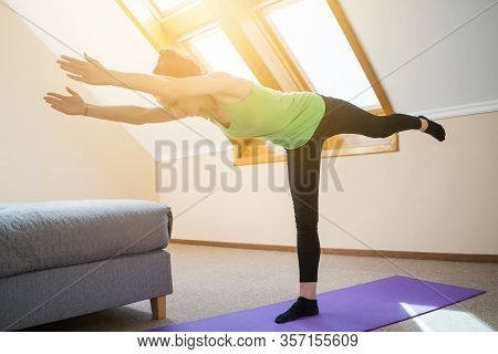 Young Woman Is Practicing Yoga At Home. Warrior Pose / Virabhadrasana