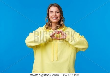 Lovely Caring Cute Blonde Girl In Yellow Hoodie Showing Heart Gesture And Smiling As Express Symapth