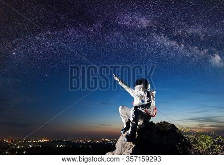 Side View Of Spaceman Pointing At Beautiful Sky With Stars While Sitting On Top Of Mountain. Mission