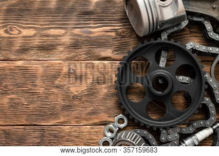 Old Car Spare Parts On Brown Wooden Workbench Flat Lay Background With Copy Space.