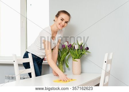 A Housewife In A Shirt Is Cleaning The House, Wipes Dust From The Table With A Cleaning Rag. A Cute