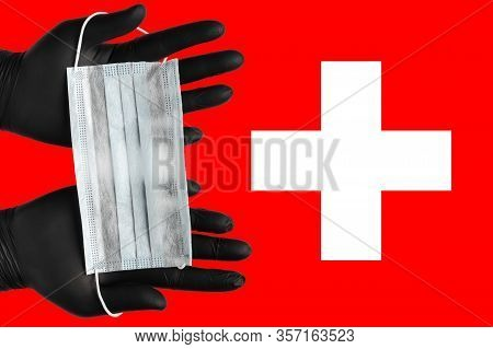 Doctor Holds Face Mask In Hands In Black Medical Gloves On Background Colors Flag Of Switzerland. Co