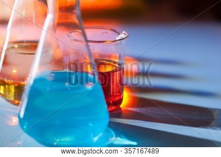 Illuminated Laboratory Flask Filed With Colorful Chemical Solutions With Shadows On The Table. Labor