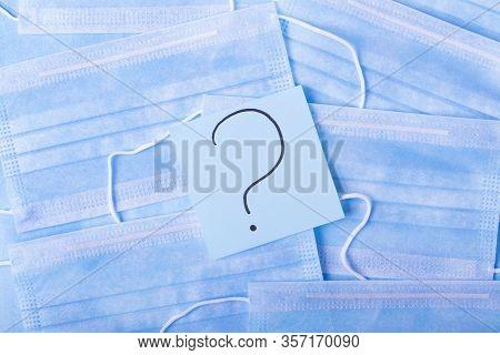 Question Mark Against The Blue Disposable Medical Masks. Shortage Concept