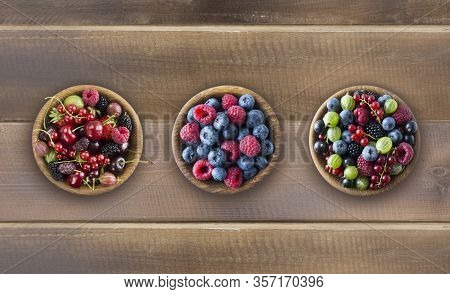 Top View. Fruits And Berries In Bowls On Wooden Background. Mixed Fruits With Copy Space For Text. M