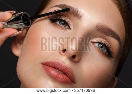 Beautiful Girl With Sexy Lips And Classic Makeup With Cosmetic Mascara Brush In Hand. Beauty Face.