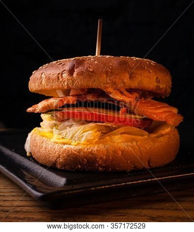 Appetizing Fish Burger With Pieces Of Red Fish Meat On A Brick Wall Background. Stock Photo Burger W