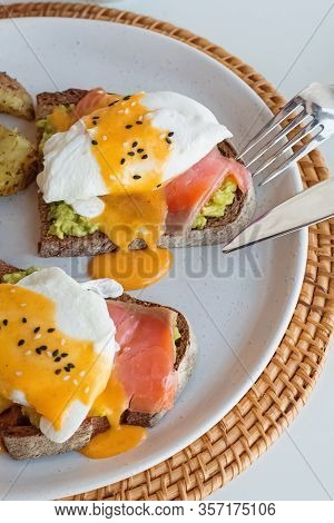 Toasts With Avocado, Salmon, Poached Egg And Hollandaise Sauce On A White Plate.