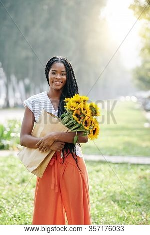 Portrait Of Beautiful Young Black Woman Standing Outdoors With Bunch On Sunflowers