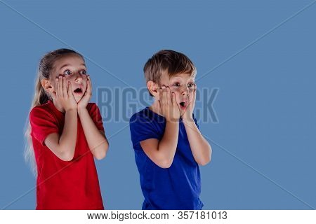 Astonished Little Girl And Boy In Casual Clothes Holding Hands On Faces And Looking Away Isolated On