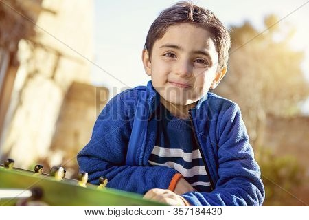 Child Leaning Against A Soccer Table Smiling