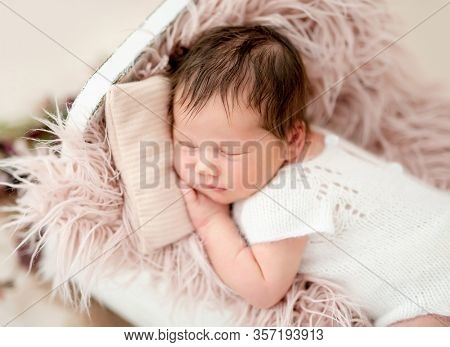 Charming newborn sleeping in tiny bed