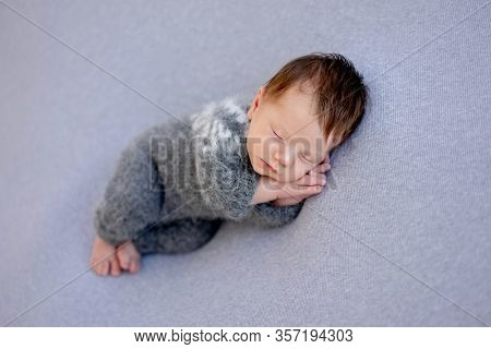 Lovely newborn in knitted suit sleeping on side