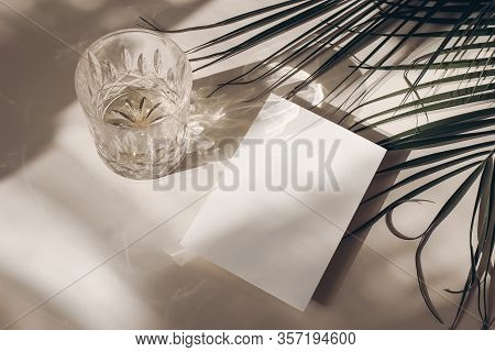 Summer Tropical Stationery Still Life Scene. Glass Of Water, Palms Leaves. Beige Table Background In