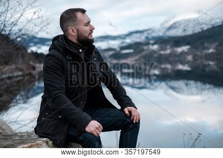 Man sitting near Hardangerfjord, Norway.