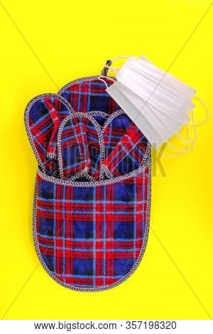 Set Of Checkered Home Slippers And Several Protective Medical Masks On Yellow Background. Hospitalit