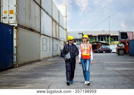 Foreman And Worker Staff Wearing A Yellow Helmet Walking In A Industrial Shipping Yard. He's Consult