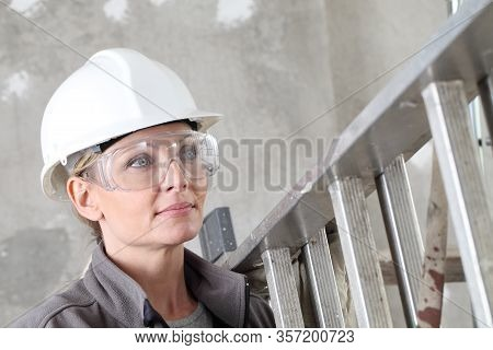 Woman Construction Worker Builder Portrait Wearing White Helmet And Protection Glasses, Holding A La