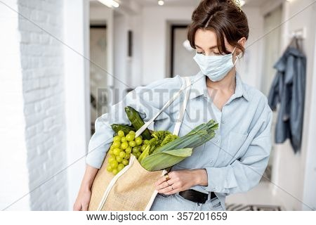 Young Woman In Medical Mask Coming Home With Shopping Bag Full Of Fresh Food. Concept Of Lifestyle D