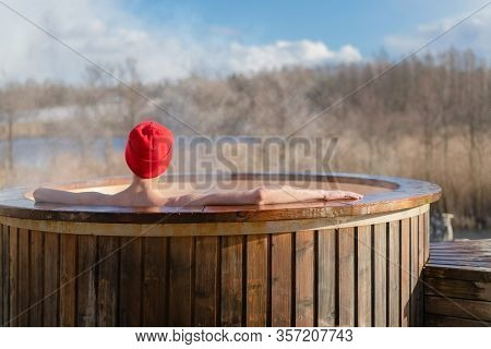 Young Adult Relaxing In Wooden Hot Tub Outside And Looking At Nature. Person Enjoying Hot Steaming P