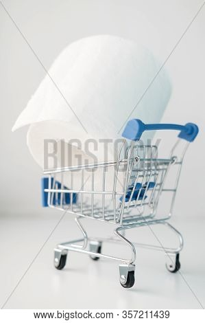 Roll Of Toilet Paper In A Decorative Shopping Trolley. Concept Of Shortage Of Goods, Panic And Paran